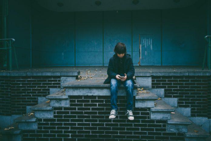 Pojke sitter på trappa och tittar i sin telefon