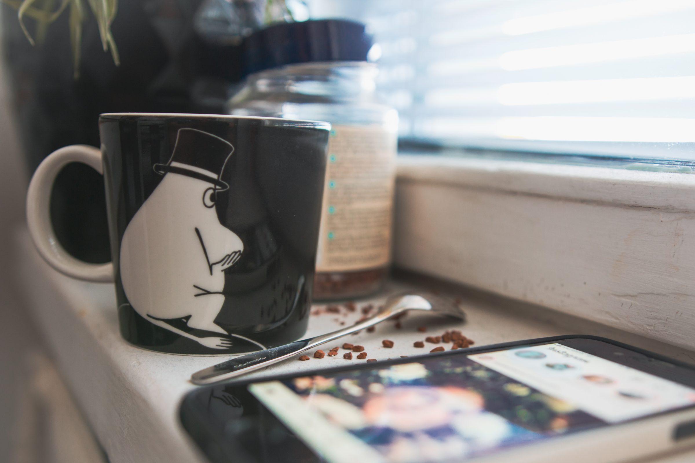 En kaffemugg bredvid en telefon på en köksyta.