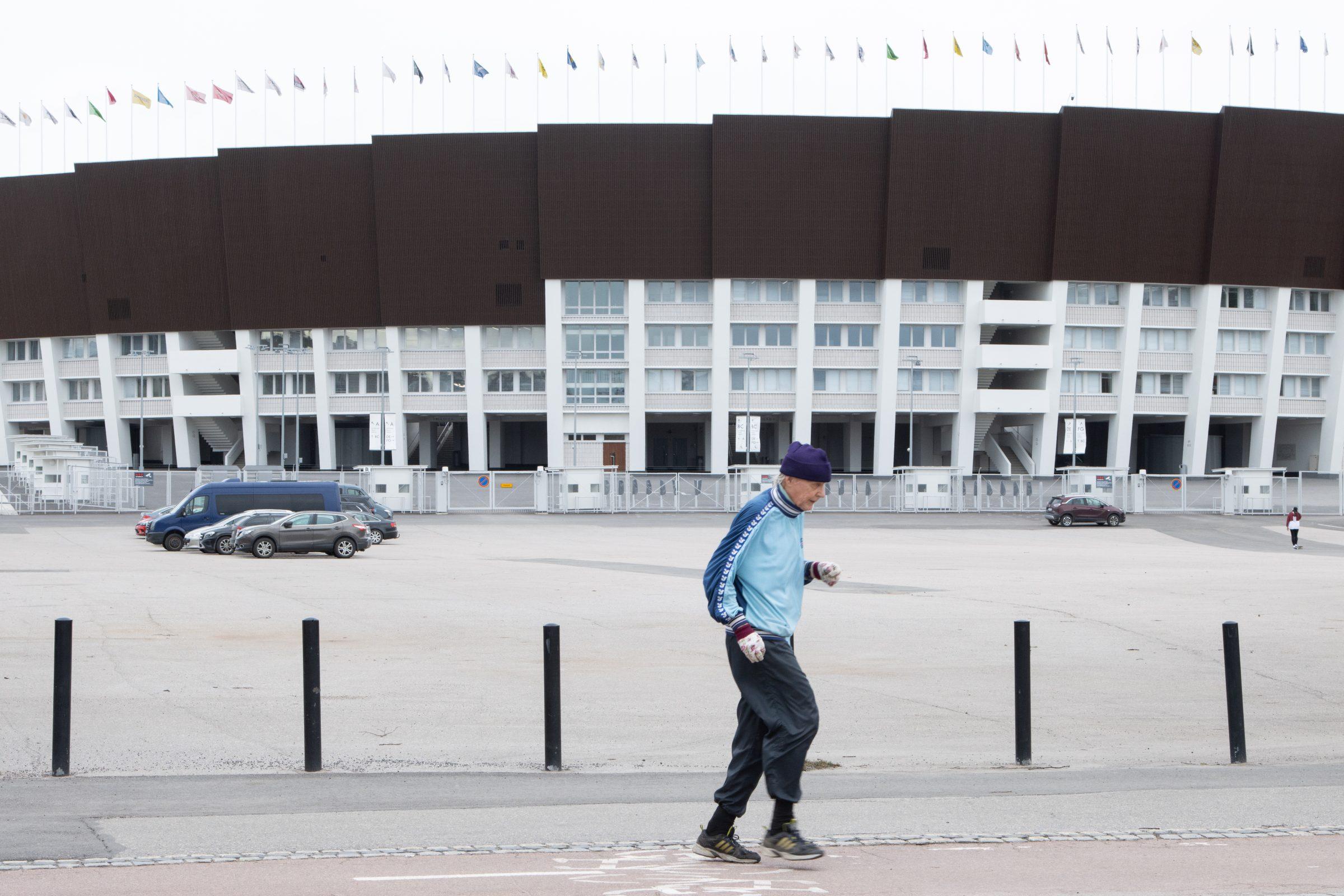 Person i blåa kläder joggar förbi Helsingfors Olympiastadion.